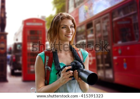 travel, tourism and people concept - happy young woman with backpack and camera photographing over london city street background - stock photo