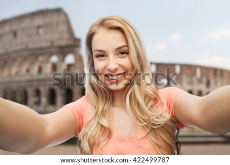 travel, tourism, emotions, expressions and people concept - happy smiling young woman taking selfie over coliseum background - stock photo