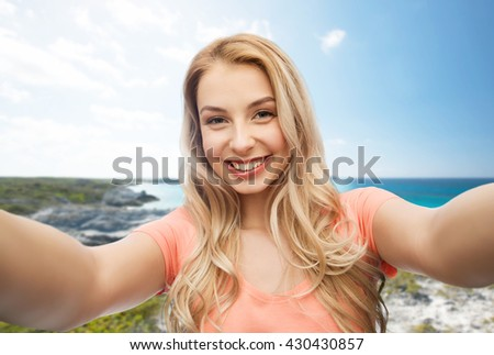 travel, tourism, emotions, expressions and people concept - happy smiling young woman taking selfie over exotic tropical beach background - stock photo