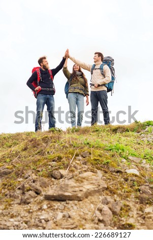 travel, tourism, hike, gesture and people concept - group of smiling friends with backpacks making high five outdoors - stock photo