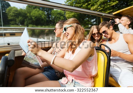 travel, tourism, summer vacation, sightseeing and people concept - group of smiling teenage friends in sunglasses with map traveling by tour bus - stock photo