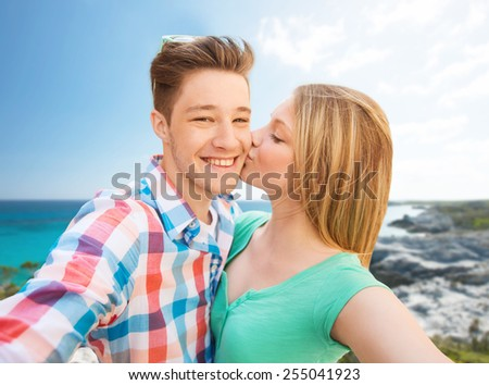 travel, tourism, summer vacation, technology and love concept - happy couple taking selfie with smartphone or camera and kissing over sea shore background - stock photo