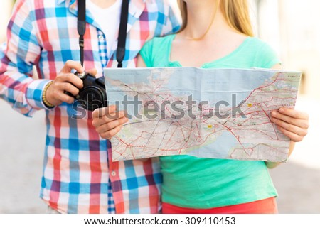 travel, tourism, technology and people concept - close up of couple with map and digital camera in city - stock photo