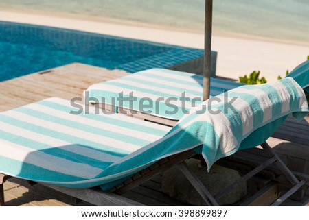 travel, tourism, vacation and summer holidays concept - parasol and sunbeds over sea and sky on maldives beach - stock photo