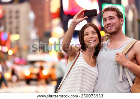 Travel tourist couple taking selfie with smartphone in New York City, USA. Self-portrait photo on Times Square at night. Beautiful young tourists having fun, Manhattan, USA. Asian woman, Caucasian man - stock photo