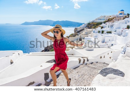 Travel Tourist Happy Woman Running Stairs Santorini, Greek Islands, Greece, Europe. Girl on summer vacation visiting famous tourist destination having fun smiling in Oia.  - stock photo