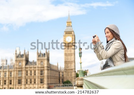 Travel tourist in london sightseeing taking photo pictures near Big Ben. Woman holding smart phone camera smiling happy near Palace of Westminster, Westminster Bridge, London, England - stock photo