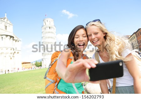 Travel tourists friends laughing taking photo with smartphone. Women girlfriends traveling in Europe smiling joyful having fun taking self-portrait picture in Pisa by Leaning Tower of Pisa, Italy. - stock photo