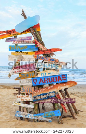 travel traffic sign stick on timber or bonfire tent at sand beach - stock photo