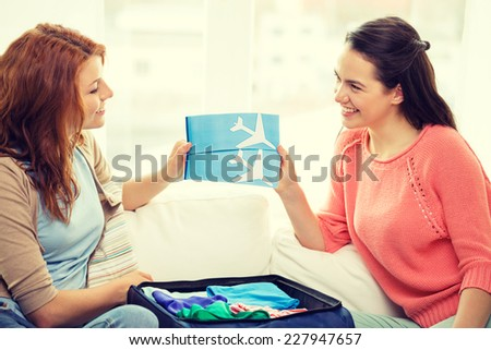 travel, vacation and friendship concept - two smiling teenage girls with plane tickets and packed suitcase - stock photo