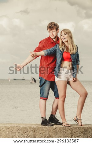 Travel vacation hitchhiking concept. Young smiling couple thumbing and hitch hiking by seaside outdoor - stock photo
