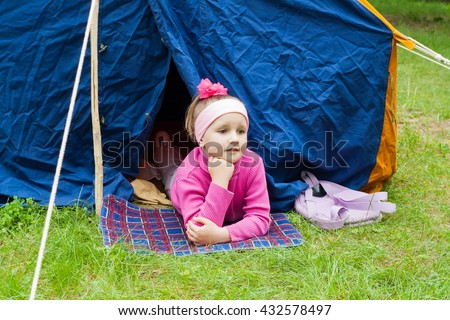 Travel with spending the night in the wood. Morning in the fresh air. Family rest . Girl young tourist. Backpacking. Tent shelter from a rain and wind. To lie on a grass . The child looks for parents - stock photo