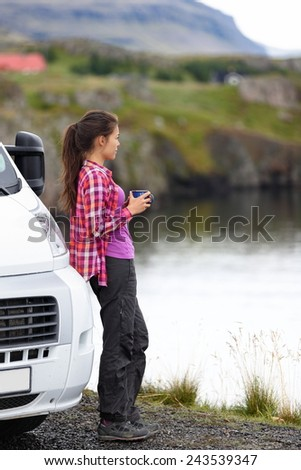 Travel woman by mobile motor home RV campervan. Traveler relaxing camping and enjoying traveling on Iceland in recreational vehicle. Girl enjoying coffee in Icelandic nature landscape. - stock photo