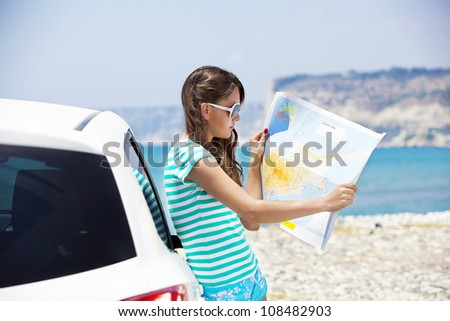 Travel - young woman with car look at road map on a beach against sea and sky - stock photo