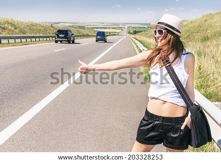 Traveler attractive smiling girl is hitchhiking along a highway in the sunny summer day. Caucasian beautiful woman has handbag. Happy female model. Travel and adventure concept. Copy space, outdoor. - stock photo