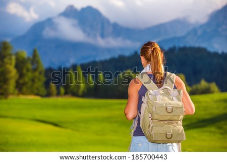Traveler girl in the mountains, rear view of woman with backpack looking on beautiful landscape, travel to Alps, summer adventure - stock photo