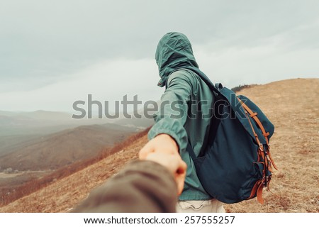Traveler man holding woman's hand and leading her on nature outdoor. Focus on man. Point of view shot - stock photo