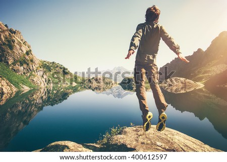 Traveler Man levitation jumping with lake and mountains on background Lifestyle Travel emotions concept outdoor  - stock photo