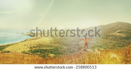 Traveler man standing with raised arms on peak of mountain near the sea and enjoying beautiful landscape in summer. Image with sunlight effect - stock photo