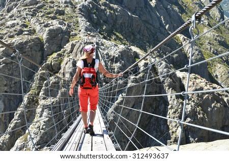Traveler on theTrift bridge. Switzerland - stock photo