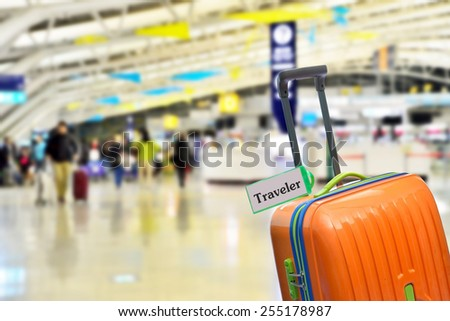 Traveler. Orange suitcase with label at airport. - stock photo