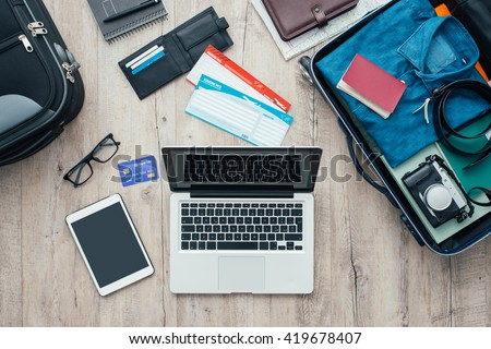 Traveler packing and getting ready for a trip, desktop with baggage, tickets, credit card, laptop and digital tablet, flat lay - stock photo