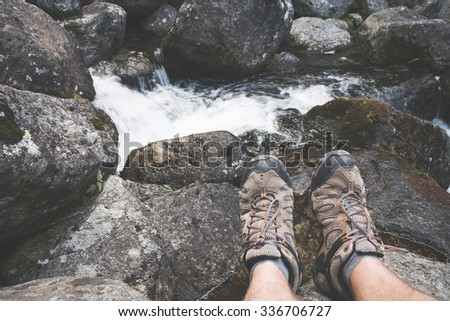 Traveler resting by the forest river, hiking shoes and man legs - stock photo