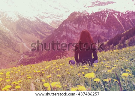 Traveler resting on grassland of mountain with vintage filter, rear view - stock photo