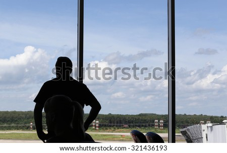 Traveler silhouettes looking at planes in the airport in Thailand - stock photo