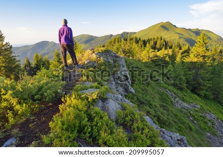 Traveler stands on a rock in the mountains on a sunny day - stock photo