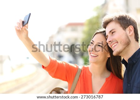 Traveler tourists couple photographing a selfie in a train station - stock photo