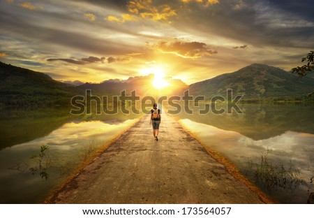 Traveler walking along the road to the mountains. - stock photo
