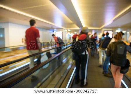 Traveler with a peoples at the speedwalk - stock photo