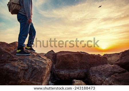 traveler with backpack on the rocks near the sea looking far away at airplane - stock photo