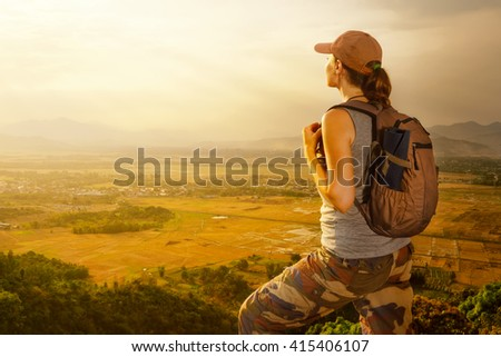 Traveler with backpack relaxing on top of a mountain and enjoying valley view during sunset.Mountains landscape, travel to Asia, happiness emotion, summer holiday concept - stock photo