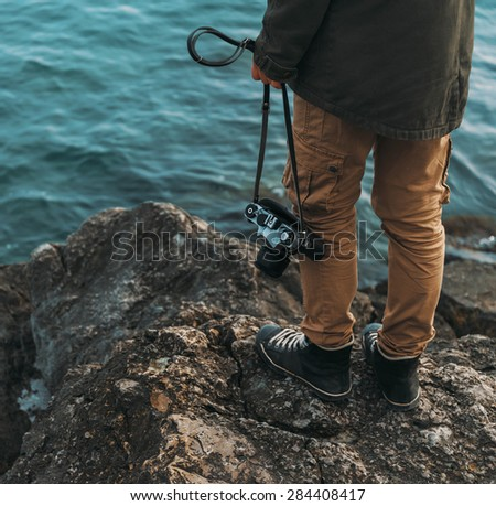 Traveler with old photo camera standing on stone coast near the sea. View of legs - stock photo