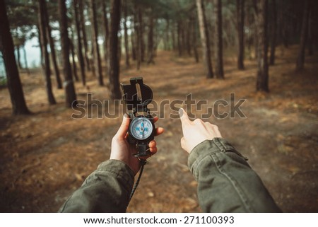 Traveler woman holding a compass and pointing direction in the forest. Close-up. Point of view shot - stock photo