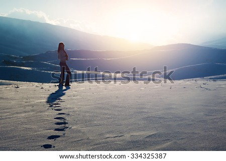 Traveler woman in the mountains, standing on snowy hill and enjoying beautiful sunset view, active winter holidays