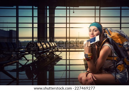 Traveler woman is waiting for a flight - stock photo