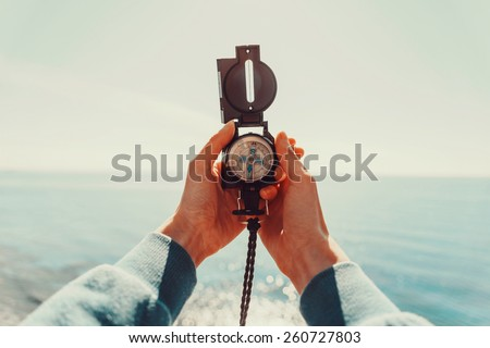 Traveler woman searching direction with a compass on background of sea. Point of view shot - stock photo