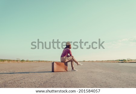 Traveler woman sits on retro suitcase and looks away on road, face is not visible - stock photo