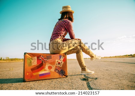 Traveler woman sits on retro suitcase and looks away on road. Suitcase with stamps flags representing each country traveled. - stock photo