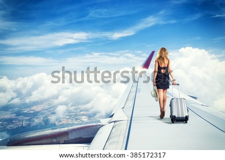 traveler woman walking on an airplane wing  carrying a suitcase Travel concept - stock photo