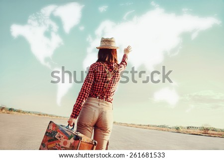 Traveler woman with vintage suitcase waves her hand to map of the world. Concept of travel - stock photo