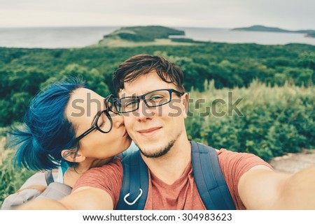 Traveler young loving couple doing selfie on nature in summer. Woman kissing a man - stock photo