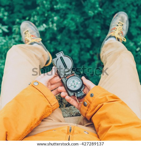 Traveler young man sitting on edge of cliff and searching direction with a compass in summer. Point of view shot - stock photo