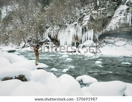 Traveler young man standing near the mountain river and taking photographs the icy waterfall in winter - stock photo