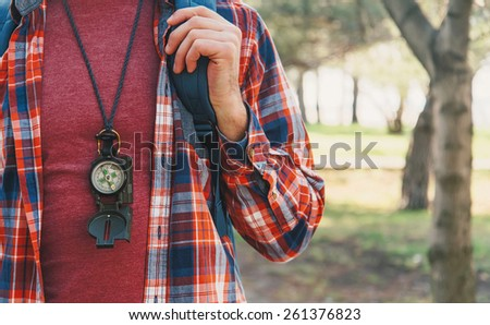 Traveler young man with backpack and compass walking in summer forest - stock photo
