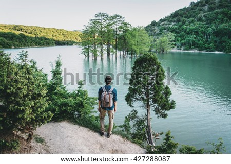 Traveler young man with backpack standing on coast of lake and enjoying view of nature, rear view - stock photo