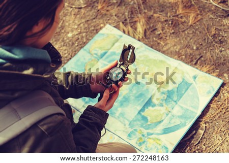 Traveler young woman searching direction with a compass on background of map outdoor. Image with instagram color effect - stock photo